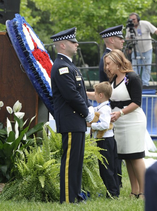 A surviving wife and son pay homage, while two police honor guards stand watch for the fallen