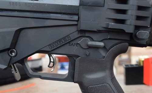 The AR-style safety lever only requires a 45-degree movement, which is beneficial to LE snipers. Note the magazine release lever to the left, the trigger, and the stock release button on the right.