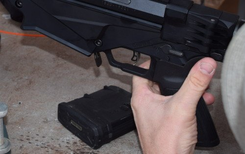 Unlocking the folding stock is accomplished by pressing a button on the stock's connection to the receiver (above my thumb).