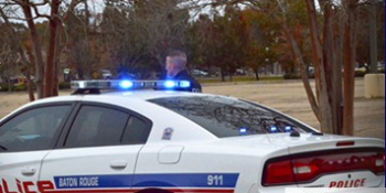 A Baton Rouge officer standing outside his patrol cruiser photo by brgov.com).