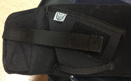 The retention strap attaches to a Velcro patch on the back of the holster but then just to the felt-like material on the outside of the backing.