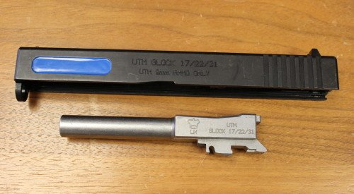 The Glock slides are clearly marked, and the barrel has modifications to prevent live ammunition being fired.