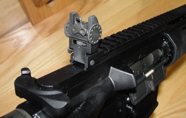 The rear sight folds down just before the charging handle. Notice the adjustable apertures.