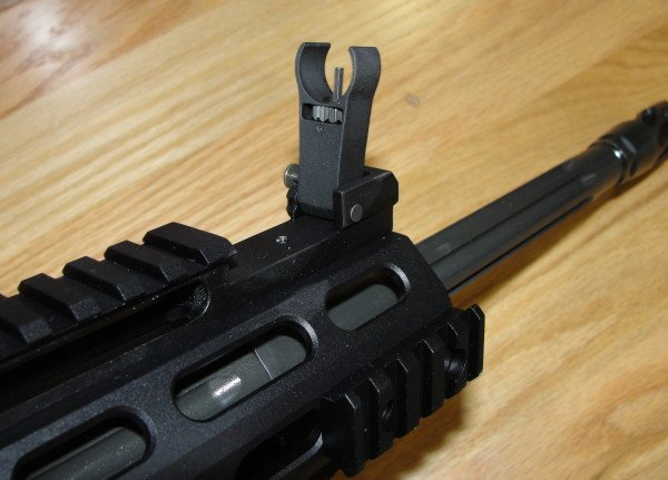 The IRS system has slots for the sights to fold down flush with the top rail.