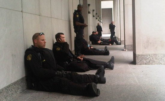 Even during protests and civil unrest, cops can become bored and complacent. (Photo - Canadian Broadcasting Corporation)
