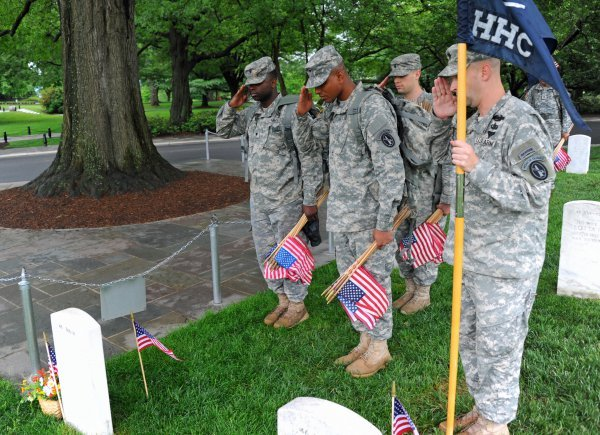 US Army soldiers placing flags at Arlington Cemetery. Photo by U.S. Military.