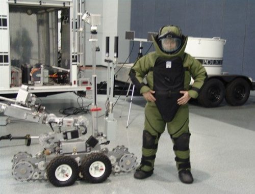 An EOD Technician with a robot used in explosives detection and disarmament.