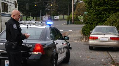 Going around the rear of the patrol car gives plenty of observation time during a passenger side approach (photo by Snohomish, WA Police).