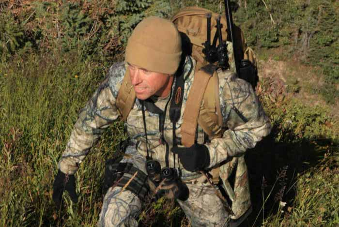 Hunter Packing a Scoped Rifle into the Woods
