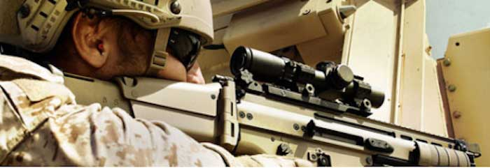 Soldier shooting SCAR rifle with 1-4x scope